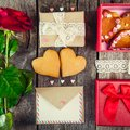 Festive composition with homemade cookies in shape of heart, rose flower, gift box. card with envelope, vintage ribbon. Gift for l Royalty Free Stock Photo