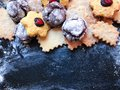 Festive cookies on a black kitchen board with powdered sugar