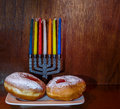 Festive donuts with jam for hanukkah appetite and menorah candles on wood background Stock Photo