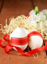Festive eggs decorated with red ribbon symbol of easter holiday Royalty Free Stock Photo