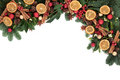 Festive fruit and spice christmas background border with cinnamon dried orange bauble decorations holly winter greenery over white Royalty Free Stock Photo