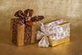 Festive gift wrapped presents two glittery golden background with copy space Royalty Free Stock Photography
