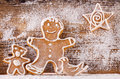 Festive gingerbread on wooden background covered with powdered sugar Royalty Free Stock Images