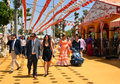 Festive goers during seville spring festival and ladies in andalusian costumes feria de abril de sevilla for articles about Stock Image
