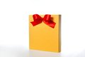 Festive gold box with a red bow on a white background Stock Photography