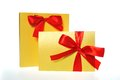Festive gold box with a red bow on white background Stock Photography