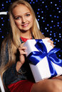 Festive photo of cute little girl with long blond hair holding a gift-box Royalty Free Stock Photo