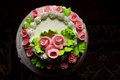 Festive pie the round cream the is decorated with cream pink rosettes Stock Photo