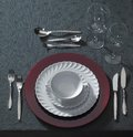 Festive place setting and candlelight classy on dark table cloth seen from above Stock Image