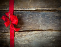 Festive red bow for a christmas card and ribbon forming border over rustic wooden planks with copyspace your greeting or Stock Photo