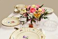 Festive table with painted golden porcelain and flowers with white tablecloth Royalty Free Stock Photo