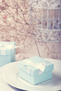 Festive table setting with blue gift on plate Royalty Free Stock Photos
