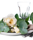 Festive table setting with floral decoration white roses leaves and berries on a white background Royalty Free Stock Photography