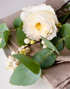 Festive table setting with floral decoration white roses leaves and berries on a white background Royalty Free Stock Images