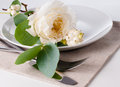 Festive table setting with floral decoration white roses leaves and berries on a white background Stock Photo