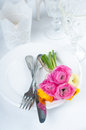 Festive table setting with flowers a bouquet of colorful buttercups vintage crockery and cutlery wedding party close up Stock Images
