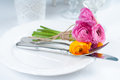 Festive table setting with flowers a bouquet of colorful buttercups vintage crockery and cutlery wedding party close up Stock Photography