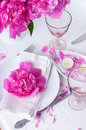 Festive table setting with pink peonies bright candles and vintage cutlery Stock Photos