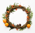 Festive wreath of vines with tangerines, thuja branches, rowanberries and cones. Flat lay, top view