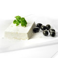 Feta cheese and black olives block of fresh with parsley garnish on grease proof paper against a white background copy space Stock Image