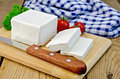 Feta cheese on a board with a knife and tomato Royalty Free Stock Photo