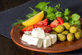 Feta cheese, tomatoes, olives and herbs in a clay plate Royalty Free Stock Photo