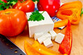 Feta cheese with vegetables on the board Stock Photography