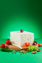 Feta cheese white arranged with tomatoes pepper chilly onion walnuts on wooden board and green background Royalty Free Stock Photos