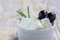 Feta slices with olives and rosemary in a white bowl on a rustic wooden table Stock Photography