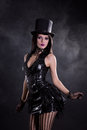 Fetish young woman in black dress and tophat studio shoot on smoky background Stock Photos