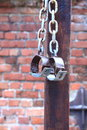 Fetters manacles on brick background old two old rusted iron rings wall Stock Photo