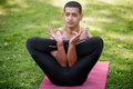 Fetus yoga posture attractive indian young man in black sport leggings practicing fitness or pilates on red mat in park doing Royalty Free Stock Image