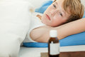 Feverish boy in bed next to medicine bottle undershirt looking over while under thick blanket on table Stock Photo