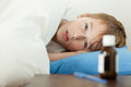 Feverish boy under thick blanket beside medicine infected young blond male child with fever laying down on blue pillow white with Stock Photos