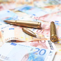 Few bullets over the pile of money Royalty Free Stock Photo