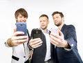 A few guys uisng their smart phones new Royalty Free Stock Photos
