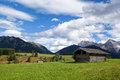 Few huts on greem meadows over blue sky in bavarian alps Royalty Free Stock Photos