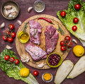Few slices of raw beef on a cutting board, around lie ingredients, fresh vegetables wooden rustic background top view Royalty Free Stock Photo