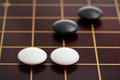 Few stones during go game playing on goban position of close up Royalty Free Stock Image