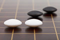 Few stones during go game playing position of on wooden board close up Stock Photos