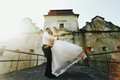 Fiance dance with a bride in the sunshine on an old bridge Royalty Free Stock Photo