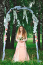 Fiancee in a pink dress and arch Stock Photo