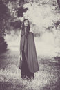 Fiction woman in cloak in forest. Royalty Free Stock Photo