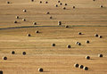 Field with big bales of straw in a random pattern