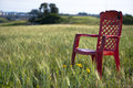 Field tranquility red plastic chair in the middle of oats on a spring sunny day peace and Stock Image