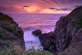 Fiery sunrise skies at minamurra headland south coast australia red and orange bath the ocean and volcanic landscape cliffs in Stock Images