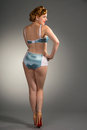 Fifties styled beautiful redheaded woman stands with back to cam of standing in blue satin lingerie Stock Photography