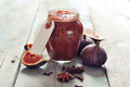 Fig jam in a glass jar with fresh figs on wooden background Stock Photos
