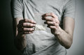 The fight against drugs and drug addiction topic addict holding package of cocaine in a gray t shirt on a dark background studio Stock Photography