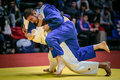 Fight on tatami two male athletes judoists in final. in background fans Royalty Free Stock Photo